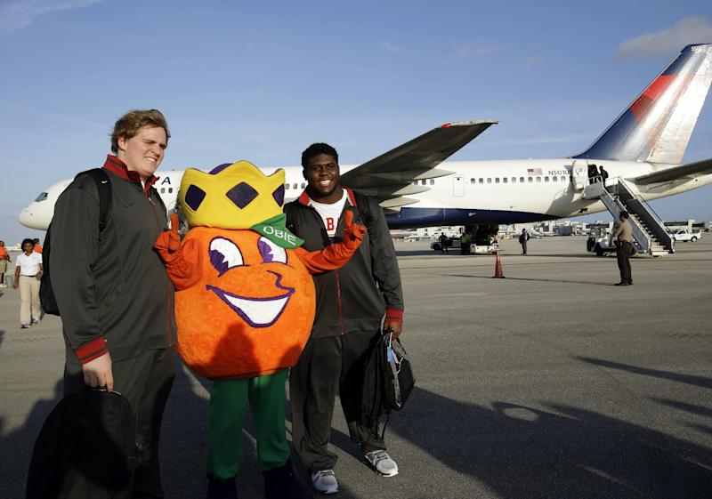Alabama's Barrett Jones, left, and Chance Warmack, right, pose with Obie, the Orange Bowl Committee mascot, upon arriving at Miami International Airport, Wednesday, Jan. 2, 2013, in Miami. Alabama is scheduled to play Notre Dame in the BCS national championship NCAA college football game next Monday. (AP Photo/Wilfredo Lee)