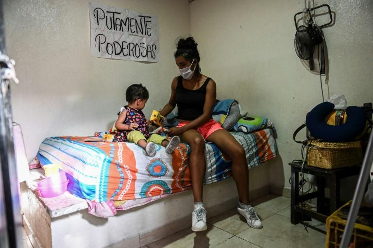 A Medellin sex worker and her young daughter sort through a food package donation (AFP Photo/Joaquin SARMIENTO)