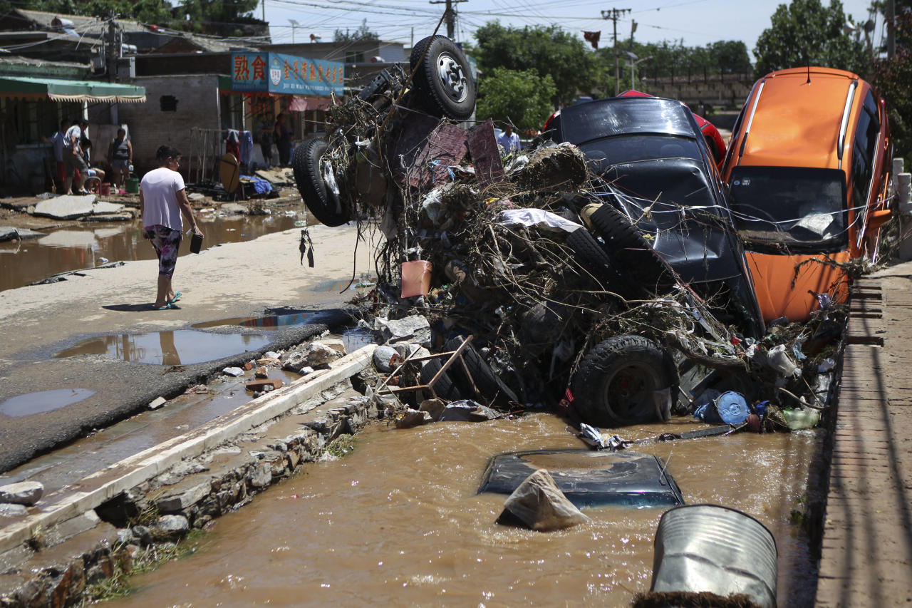 In this Sunday, July 22, 2012 photo, vehicles destroyed in a flood pile up in a ditch in Fangshan district of Beijing, China. As China's flood-ravaged capital dealt with the aftermath of the heaviest rain in six decades Monday, including the deaths of 37 people, questions were being raised about whether the city's push for modernization came at the expense of basic infrastructure such as drainage networks. (AP Photo) CHINA OUT