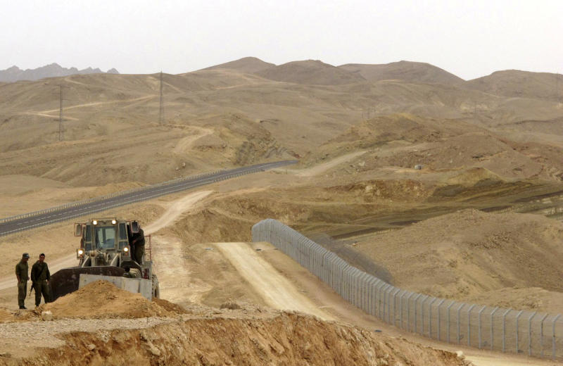 FILE - In this Feb. 15, 2012 photo, an Israeli bulldozer works at the site where Israel builds a barrier along the border with Egypt in southern Israel. The number of Africans slipping into Israel from Egypt's Sinai desert has dropped dramatically from about 1,000 a month in recent months to 268 in July 2012, with the government crediting a soon-to-be-completed border fence and a new, get-tough policy of detaining migrants who show up at the Israeli border. (AP Photo/Diaa Hadid, File)