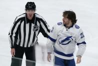 Linesmen Pierre Racicot, left, escorts Tampa Bay Lightning's Brayden Point (21) to the penalty box after Point and Dallas Stars' Andrew Cogliano fought in the third period of an NHL hockey game in Dallas, Tuesday, March 2, 2021. (AP Photo/Tony Gutierrez)