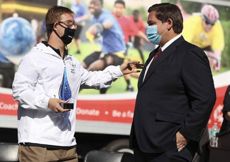 FILE - In this Nov. 19, 2020, file photo, athlete Chris Nikic, left, reaches out to Florida Gov. Ron DeSantis during a Special Olympics USA Games event at Special Olympics Florida Headquarters in Clermont, Fla. (Stephen M. Dowell/Orlando Sentinel via AP, File)