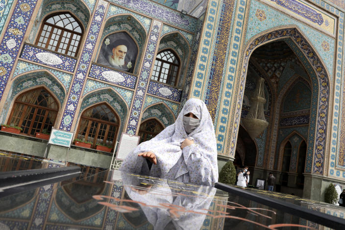 A woman prays at the grave of an unknown soldier who was killed during 1980-88 Iran-Iraq war, at the shrine of Saint Saleh in northern Tehran, Iran, Tuesday, April 6, 2021. .(AP Photo/Vahid Salemi)