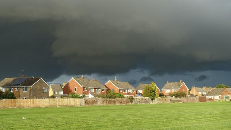 Dark gray storm clouds gather above houses in a village.