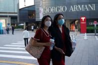 People wearing face masks following the COVID-19 outbreak walk past a store of Italian luxury Giorgio Armani at a shopping complex in Beijing