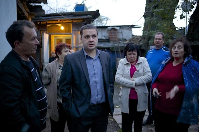 In this photo taken on Wednesday, Nov. 27, 2013, Igor Zarytovsky, center, and his father Vladimir, left, gather with their neighbors in the yard of the railroad house in the village of Vesyoloye outside Sochi, Russia. As the Winter Games are getting closer, many Sochi residents are complaining that their living conditions only got worse and that authorities are deaf to their grievances. (AP Photo/Alexander Zemlianichenko)