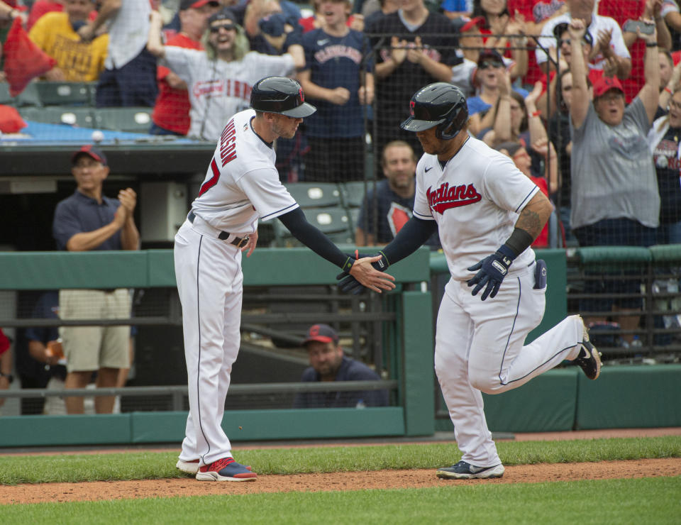 Cleveland Indians' Harold Ramirez, right, is greeted by third base coach Kyle Hudson after hitting a solo home run off Chicago White Sox relief pitcher Craig Kimbrel during the eighth inning of a baseball game in Cleveland, Sunday, Sept. 26, 2021. (AP Photo/Phil Long)