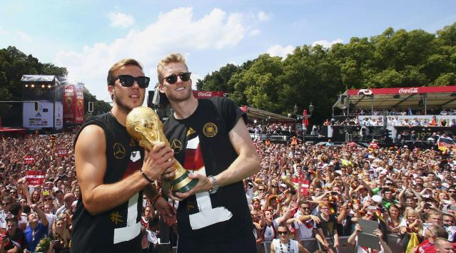 Germany's Mario Goetze (L) and Andre Schuerrle pose with the World Cup trophy during celebrations to mark the team's 2014 Brazil World Cup victory, at a 'fan mile' public viewing zone in Berlin July 15, 2014. Germany's victorious soccer team led by coach Joachim Loew returned home on Tuesday after winning the 2014 Brazil World Cup. A triumphant Germany team landed in Berlin on Tuesday to a hero's welcome, greeted by hundreds of thousands of jubilant Germans waving flags and wearing the national colours, revelling in the nation's fourth World Cup victory on Sunday in Brazil. REUTERS/Alex Grimm/Pool (GERMANY - Tags: SPORT SOCCER WORLD CUP TPX IMAGES OF THE DAY)