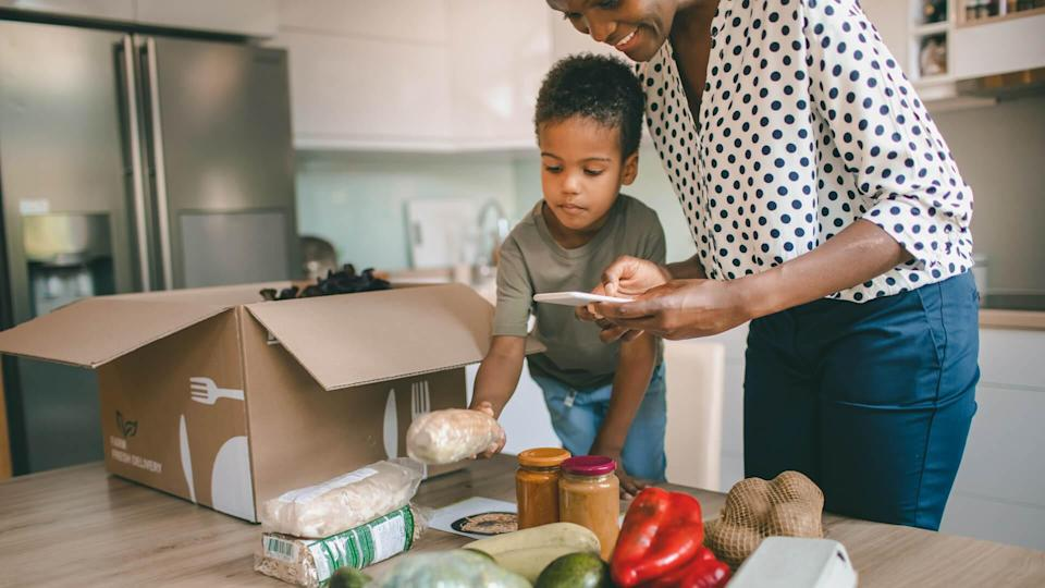Mother and her son opening parcel with meal kit in their kitchen.