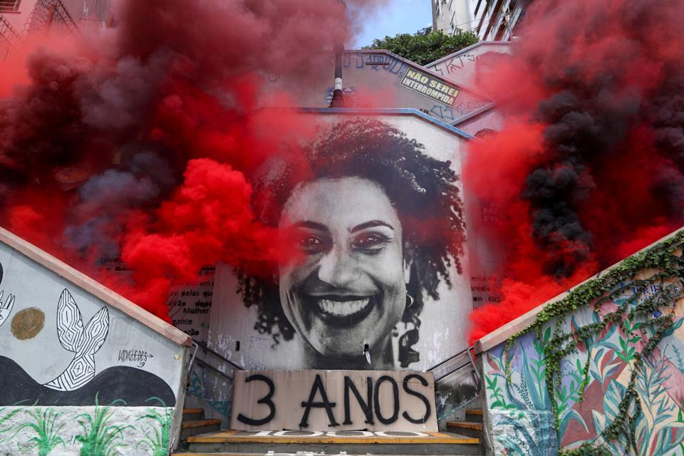 Smoke is released in an antifascist act near an image of late human rights activist and councilwoman Marielle Franco, to mark the three-year anniversary of her murder in Sao Paulo, Brazil March 14, 2021. REUTERS/Amanda Perobelli     TPX IMAGES OF THE DAY