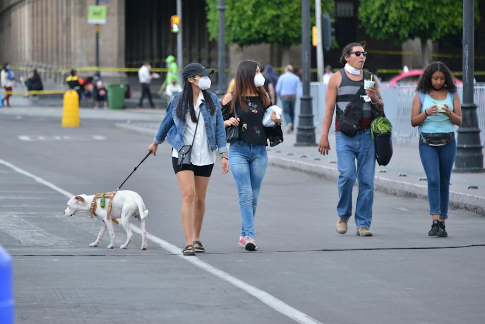 A woman wears a face mask while takes her dog for a walk amid the daily life of the  COVID-19 pandemic, the commercial business are beginning to break free of lockdown on June 25, 2020 in Mexico City, Mexico. (Photo: Carlos Tischler / Eyepix Group/Barcroft Media via Getty Images)