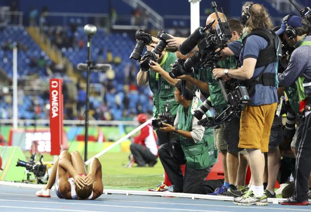 2016 Rio Olympics - Athletics - Women's Heptathlon 800m - Olympic Stadium - Rio de Janeiro, Brazil - 13/08/2016. Photographers work around Jessica Ennis-Hill (GBR) of Great Britain as she lies on the tracks. REUTERS/Lucy Nicholson FOR EDITORIAL USE ONLY. NOT FOR SALE FOR MARKETING OR ADVERTISING CAMPAIGNS.