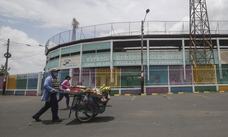 Street vendors push their fruit for sale outside Roberto Clemente baseball stadium in Masaya, Nicaragua, Thursday, May 28, 2020. As the new coronavirus spread and economies shut across Latin America, Nicaragua stayed open _ schools, stores, concert halls, and baseball stadiums, all operating uninterrupted on orders of a government that denied the gravity of the disease.   (AP Photo/Alfredo Zuniga)