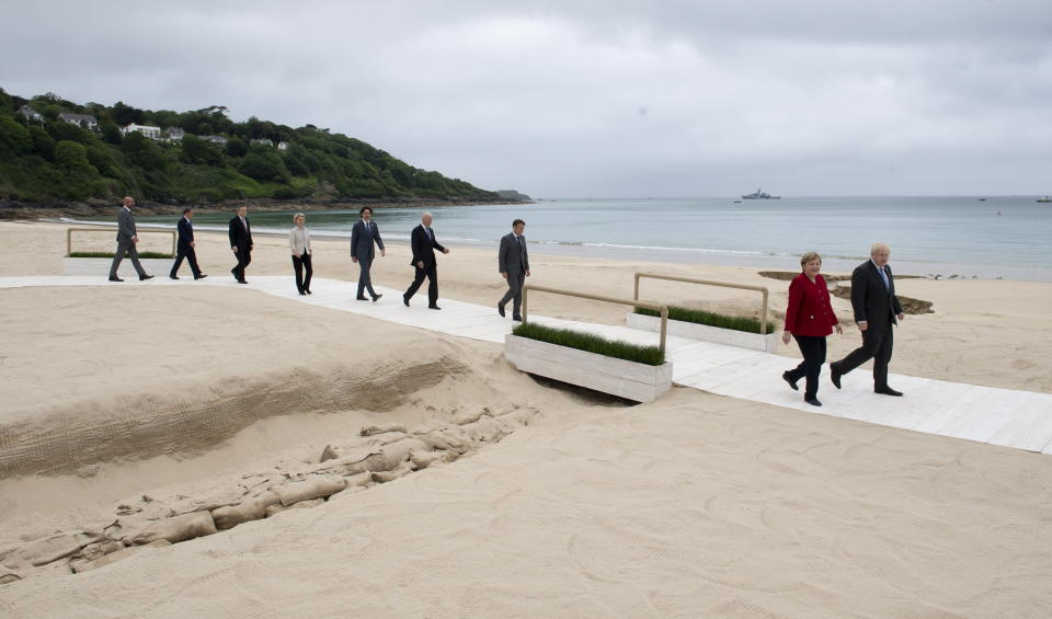 United Kingdom Prime Minister Boris Johnson and German Chancellor Angela Merkel walk with French President Emmanuel Macron, U.S. President Joe Biden, Canadian Prime Minister Justin Trudeau, European Commission President Ursula von der Leyen, Italian Prime Minister Mario Draghi, Japanese Prime Minister Yoshihide Suga and European Council President Charles Michel to the family photo at the G7 Summit in Carbis Bay, England on Friday June 11, 2021. (Adrian Wyld/The Canadian Press via AP)
