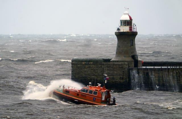 A pilot boat heads out of the Tyne, past South Shields lighthouse, in choppy conditions