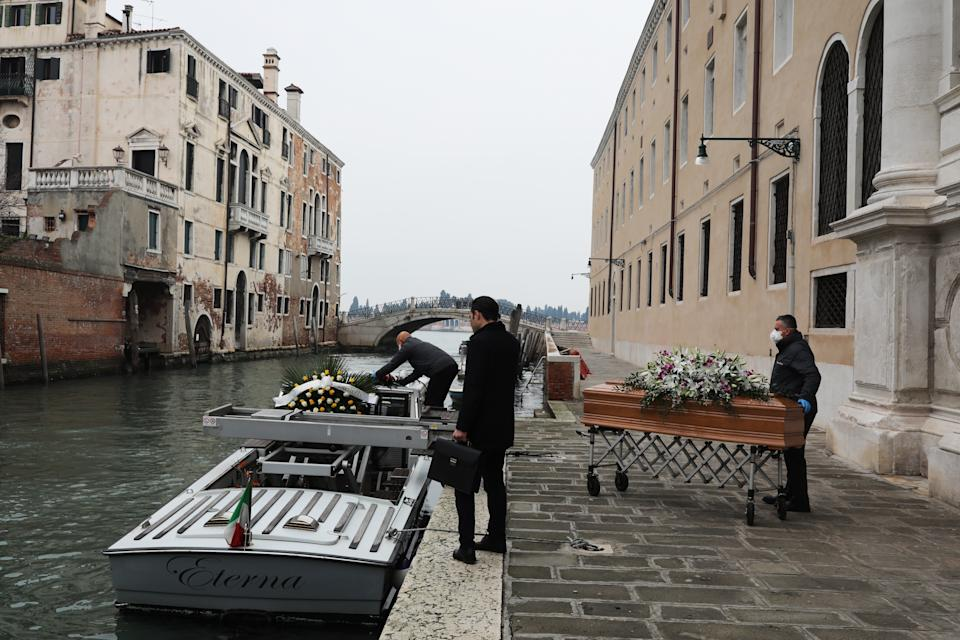 VENICE, ITALY - MARCH 10: A coffin is brought out of the hospital in the presence of the funeral home employee, to be loaded onto the funeral boat towards the cemetery on March 10, 2020 in Venice, Italy. According to the funeral home, the deceased was a 60-year-old woman who died of breast cancer. Due to the Coronavirus, funerals have been canceled all over the country like other religious ceremonies and weddings, as a result the bodies of the deceased are brought directly from the funeral chamber of the hospitals to the cemeteries for burial, where only close relatives can attend. The Italian Government has taken the unprecedented measure of a nationwide lock-down, in an effort to fight the world's second-most deadly coronavirus outbreak outside of China.The movements in and out are allowed only for work reasons, health reasons proven by a medical certificate. (Photo by Marco Di Lauro/Getty Images)