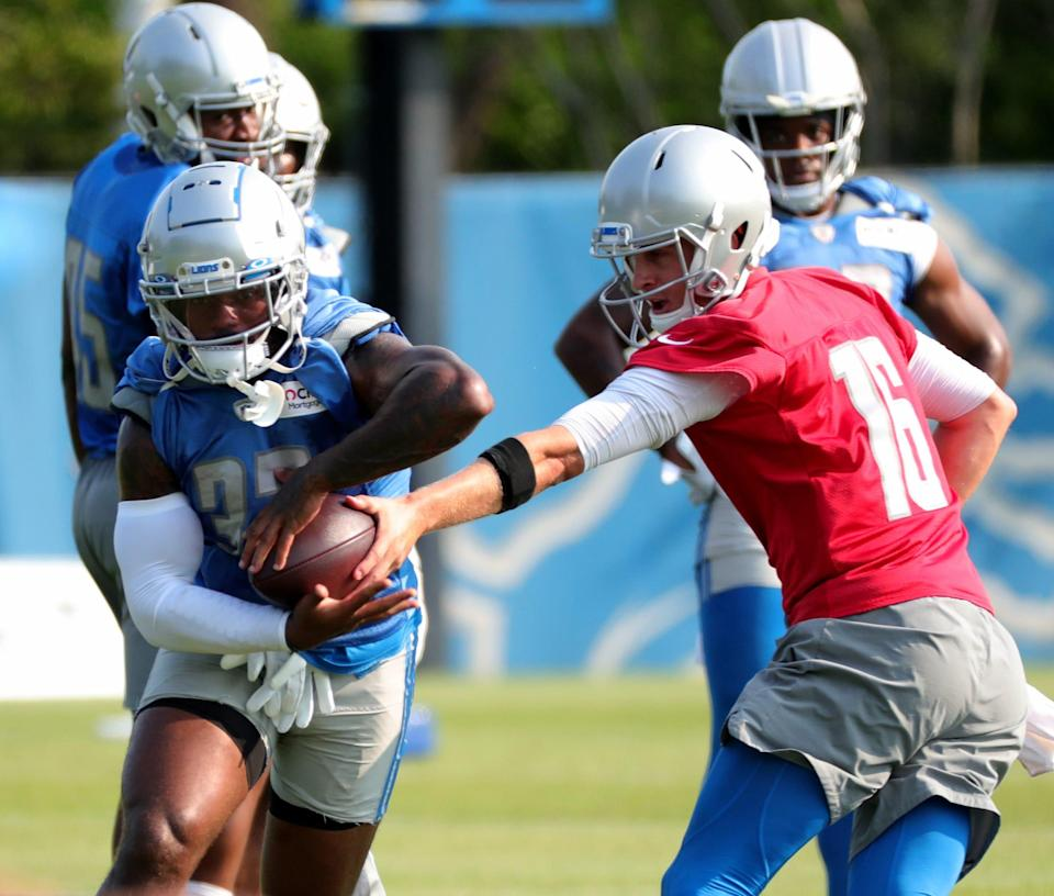 Detroit Lions quarterback Jared Goff hands off to running back D'Andre Swift during training camp Saturday 31, 2021 at the Allen Park facility.