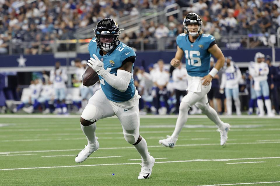 Jaguars running back Carlos Hyde (24) runs the ball after taking the hand off from quarterback Trevor Lawrence during Sunday's preseason game against the Cowboys.
