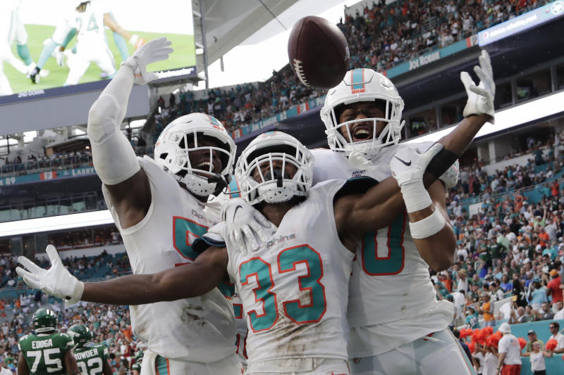 Miami Dolphins' outside linebacker Jerome Baker (55) cornerback Jomal Wiltz (33) and defensive back Nik Needham (40) celebrate after Wiltz made an interception during the first half of an NFL football game against the New York Jets, Sunday, Nov. 3, 2019, in Miami Gardens, Fla. (AP Photo/Lynne Sladky)
