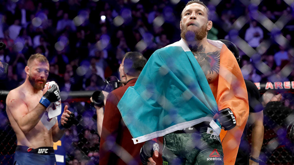 Conor McGregor walks across the Octagon after defeating Donald Cerrone (L) in a welterweight bout during UFC246 at T-Mobile Arena on January 18, 2020.