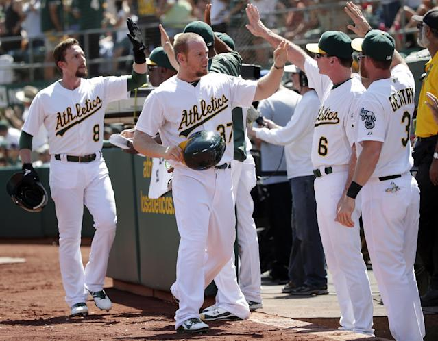 Oakland Athletics' Jed Lowrie (8) and Brandon Moss, center, are high-fived after scoring on single from Geovany Soto during the first inning of a baseball game on Monday, Sept. 1, 2014, in Oakland, Calif. (AP Photo/Marcio Jose Sanchez)