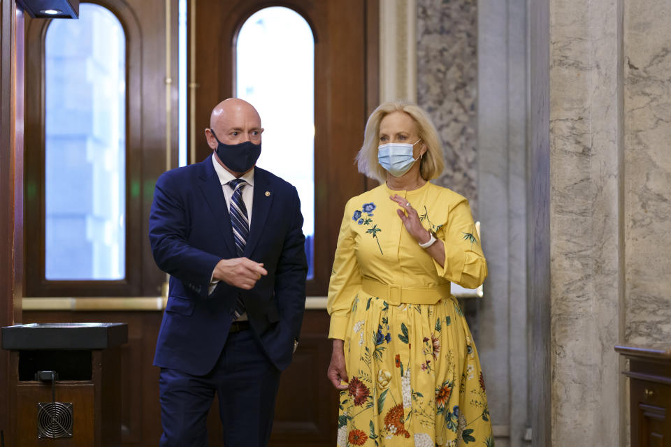 Sen. Mark Kelly, D-Ariz., is joined by Cindy McCain, right, the widow of the late Senator John McCain of Arizona, as Kelly arrives to deliver his maiden speech to the Senate, at the Capitol in Washington, Wednesday, Aug. 4, 2021. (AP Photo/J. Scott Applewhite)