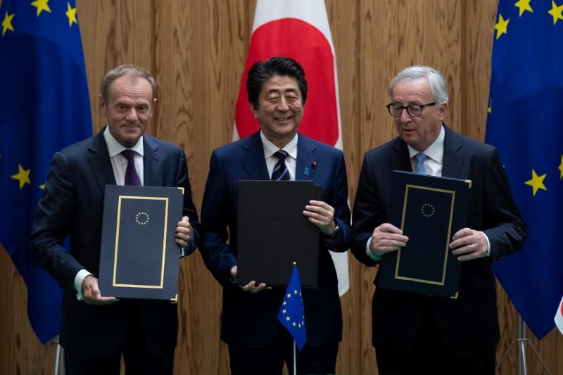 Japanese Prime Minister Shinzo Abe poses after signing a contract with European Commission President Jean-Claude Juncker and European Council President Donald Tusk at the Japanese Prime Minister's office in Tokyo