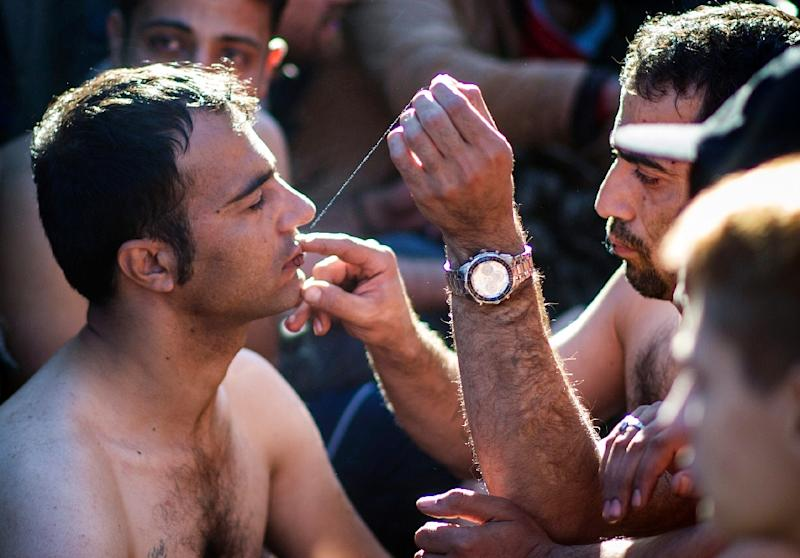 A man sews shut the mouth of a fellow migrant from Iran in protest at being held up at the Greece-Macedonia border near Gevgelija on November 23, 2015 (AFP Photo/Robert Atanasovski)