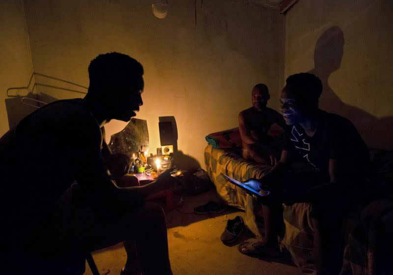 FILE PHOTO: Friends talk by candle light during load shedding in Embo
