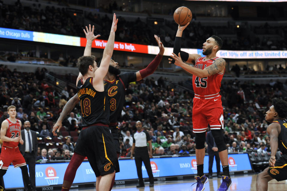 Chicago Bulls' Denzel Valentine (45) shoots Cleveland Cavaliers' Andre Drummond (3) and Matthew Dellavedova (18) during the second half of an NBA basketball game Tuesday, March 10, 2020, in Chicago. (AP Photo/Paul Beaty)