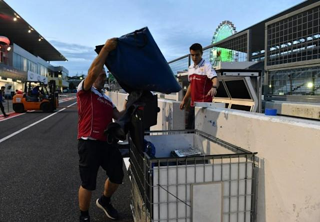 Alfa Romeo team mechanics pack away pit lane equipment ahead of the arrival of Typhoon Hagibis at Suzuka (AFP Photo/TOSHIFUMI KITAMURA)