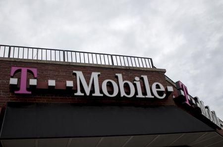 FILE PHOTO: People pass by a T-Mobile store in the Brooklyn borough of New York