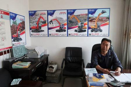 Wang Chenglin, who runs a construction machinery distributor, poses for a picture at his office in Dandong