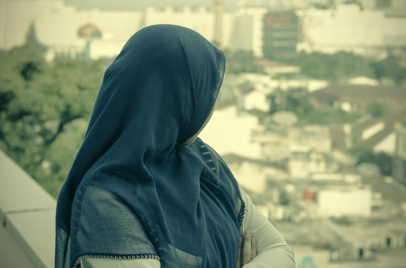Pictured is a stock image of a woman in a dark blue hijab looking over a city.