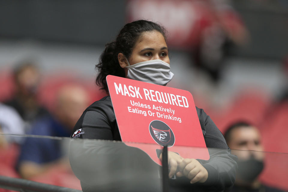 ATLANTA, GA - OCTOBER 25:  A stadium employee holds up a sign about wearing masks during the week 7 NFL game between the Atlanta Falcons and the Detroit Lions on October 25, 2020 at Mercedes-Benz Stadium in Atlanta, Georgia.  (Photo by David John Griffin/Icon Sportswire via Getty Images)