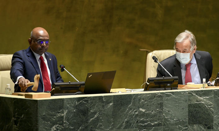 In this photo provided by United Nations, Abdulla Shahid, left, pounds the gavel signaling his start as the new president of the 76th session of the United Nations General Assembly, accompanied by Secretary-General António Guterres at U.N. headquarters on Tuesday, Sept. 14, 2021. (Evan Schneider/United Nations via AP)