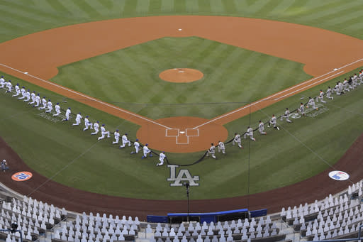 Members of the Los Angeles Dodgers and the San Francisco Giants kneel during a moment of silence prior to an opening day baseball game Thursday, July 23, 2020, in Los Angeles. (AP Photo/Mark J. Terrill)