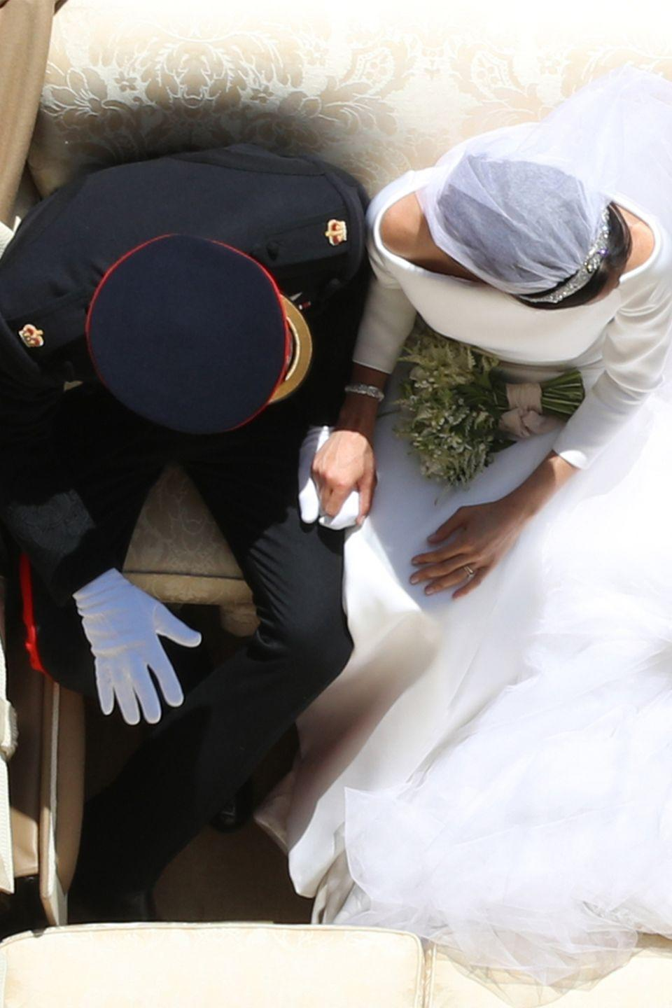 <p>The Duke and Duchess of Sussex held hands during a carriage procession ride after their wedding ceremony. </p>