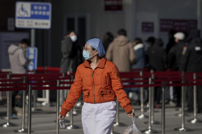 A nurse wearing a face mask to help curb the spread of the coronavirus walks by people lining up for a coronavirus test at a hospital in Beijing, Sunday, Jan. 17, 2021. The coronavirus was found on ice cream produced in eastern China, prompting a recall of cartons from the same batch, according to the government. (AP Photo/Andy Wong)