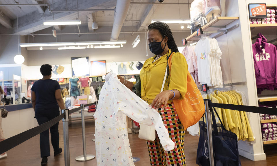 A woman shops for clothing in a Gap store during the coronavirus pandemic, in New York. (AP Photo/Mark Lennihan, File)