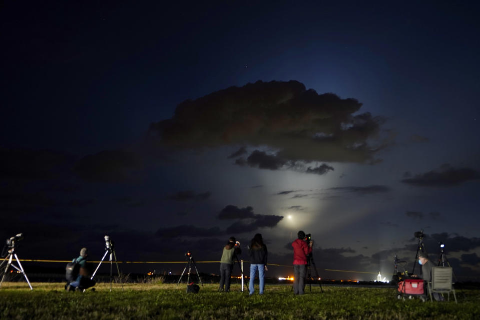 Photographers watch SpaceX Falcon 9 rocket with the Crew Dragon space capsule lift off from pad 39A at the Kennedy Space Center in Cape Canaveral, Fla., Friday, April 23, 2021. (AP Photo/Brynn Anderson)
