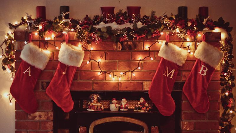 Red Christmas stockings hang above a fireplace with decorations on the mantle