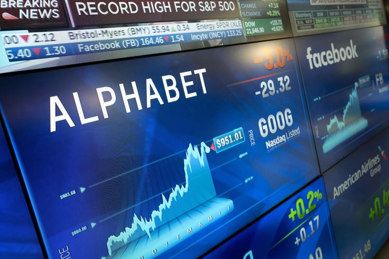FILE - In this July 25, 2017, file photo, Alphabet stock is shown on a screen at the Nasdaq MarketSite in New York. Shares in Google parent Alphabet jumped in after-hours trading Monday, July 23, 2018, as the company's second-quarter results exceeded Wall Street forecasts after taking into account a $5 billion charge levied by European regulators. (AP Photo/Mark Lennihan, File)