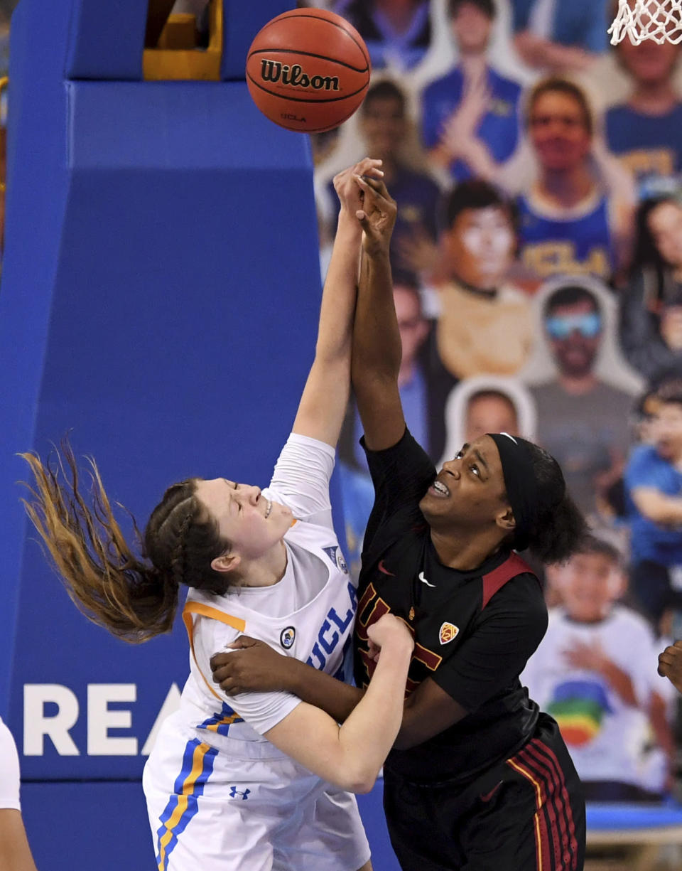 UCLA's Lindsey Corsaro, left, fights for the rebound against Southern California's Jordyn Jenkins, right, in the second half of an NCAA college basketball game at Pauley Pavilion in Westwood, Calif., Friday, Feb. 26, 2021. (Keith Birmingham/The Orange County Register via AP)