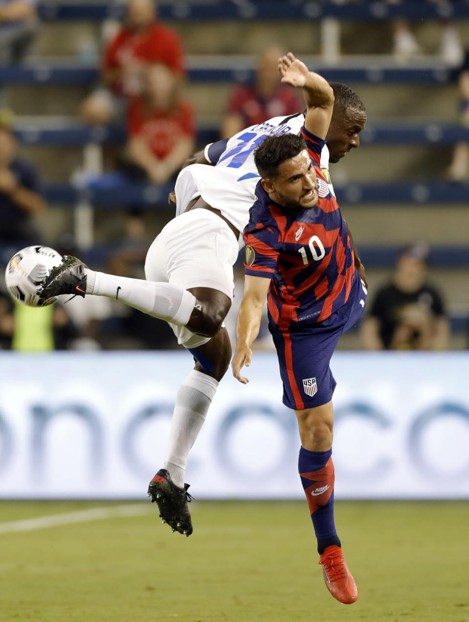 Martinique defender Sebastien Cretinoir (21) and U.S. midfielder Cristian Roldan (10) collide after attempting to head the ball during the first half of a CONCACAF Gold Cup soccer match in Kansas City, Kan., Thursday, July 15, 2021. (AP Photo/Colin E. Braley)