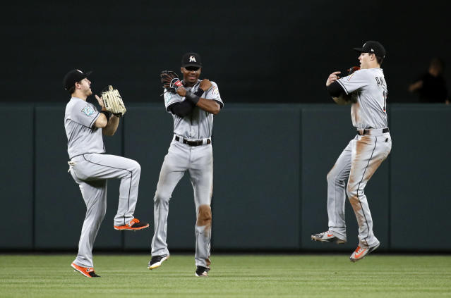 From left to right, Miami Marlins left fielder J.B. Shuck, center fielder Lewis Brinson and right fielder Brian Anderson celebrate after a baseball game against the Baltimore Orioles, Friday, June 15, 2018, in Baltimore. (AP Photo/Patrick Semansky)