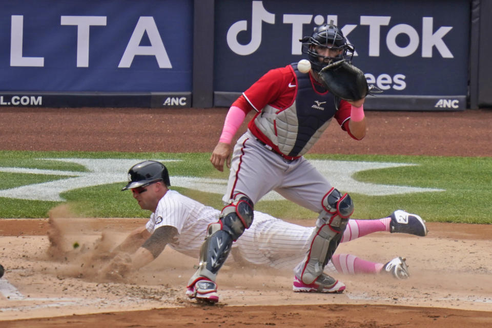 Washington Nationals catcher Yan Gomes, front, waits for the ball while New York Yankees' Brett Gardner slides safely home during the third inning of a baseball game at Yankee Stadium, Sunday, May 9, 2021, in New York. (AP Photo/Seth Wenig)
