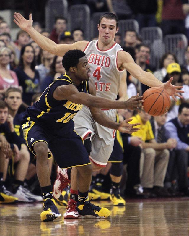 Michigan's Derrick Walton, left, passes the ball around Ohio State's Aaron Craft during the second half of an NCAA college basketball game Tuesday, Feb. 11, 2014, in Columbus, Ohio. Michigan beat Ohio State 70-60. (AP Photo/Jay LaPrete)