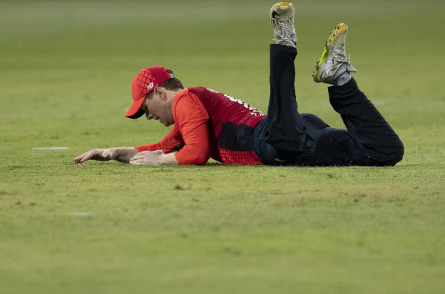 England's captain Eoin Morgan falls on the ground after attempting a catch during the 2nd T20 cricket match between South Africa and England at Kingsmead stadium in Durban, South Africa, Friday, Feb. 14, 2020. (AP Photo/Themba Hadebe)