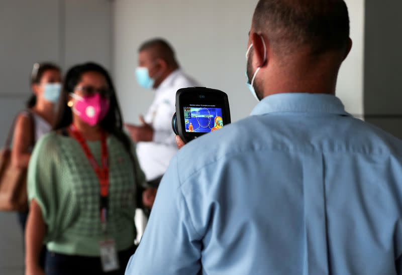 FILE PHOTO: An employee measures the temperatures of travelers at the Tocumen International Airport during the coronavirus disease (COVID-19) outbreak, in Panama City